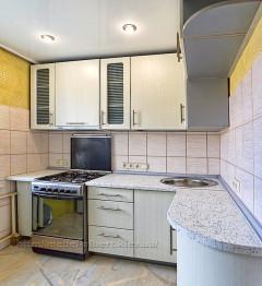 Угловая кухня для хрущевки с разной шириной столешниц и радиусным фасадом.